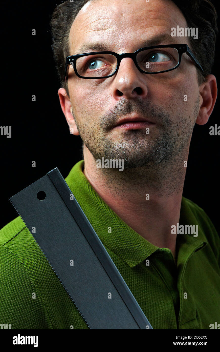 Man with a saw in his hand - Stock Image