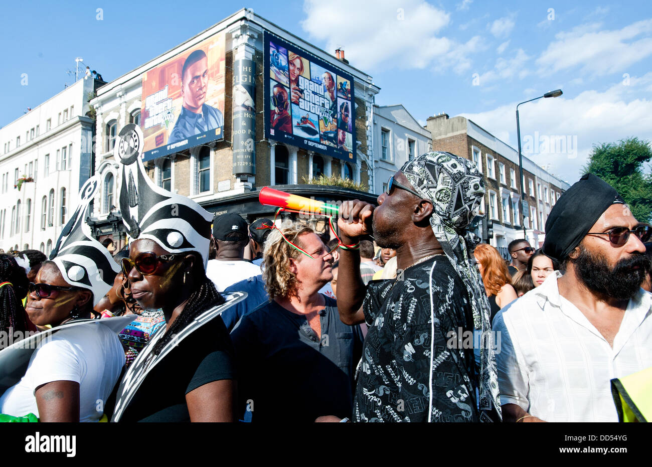 London, UK - 26 August 2013: a man plays a horn during the annual parade at the Notting Hill Carnival. - Stock Image