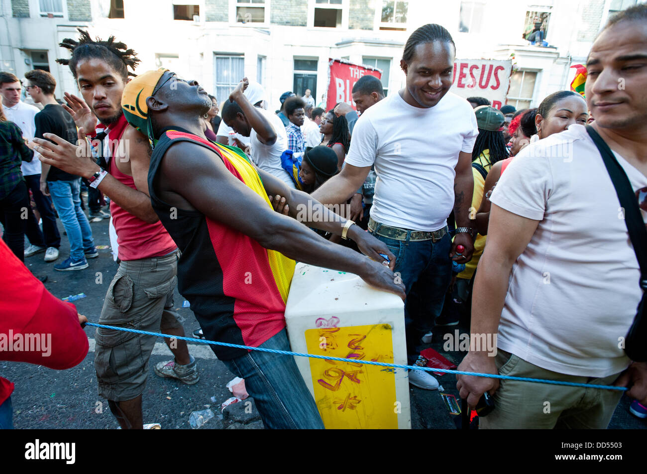 London, UK - 26 August 2013: a man dances with a traffic divider during the  annual parade at the Notting Hill Carnival. - Stock Image