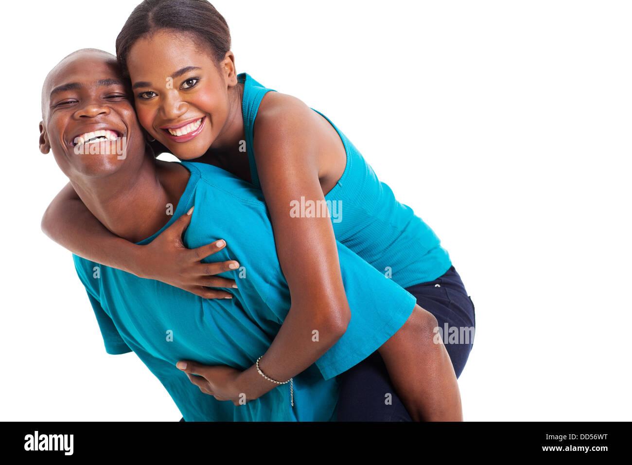 cheerful African woman enjoying piggyback ride on boyfriends back isolated on white - Stock Image