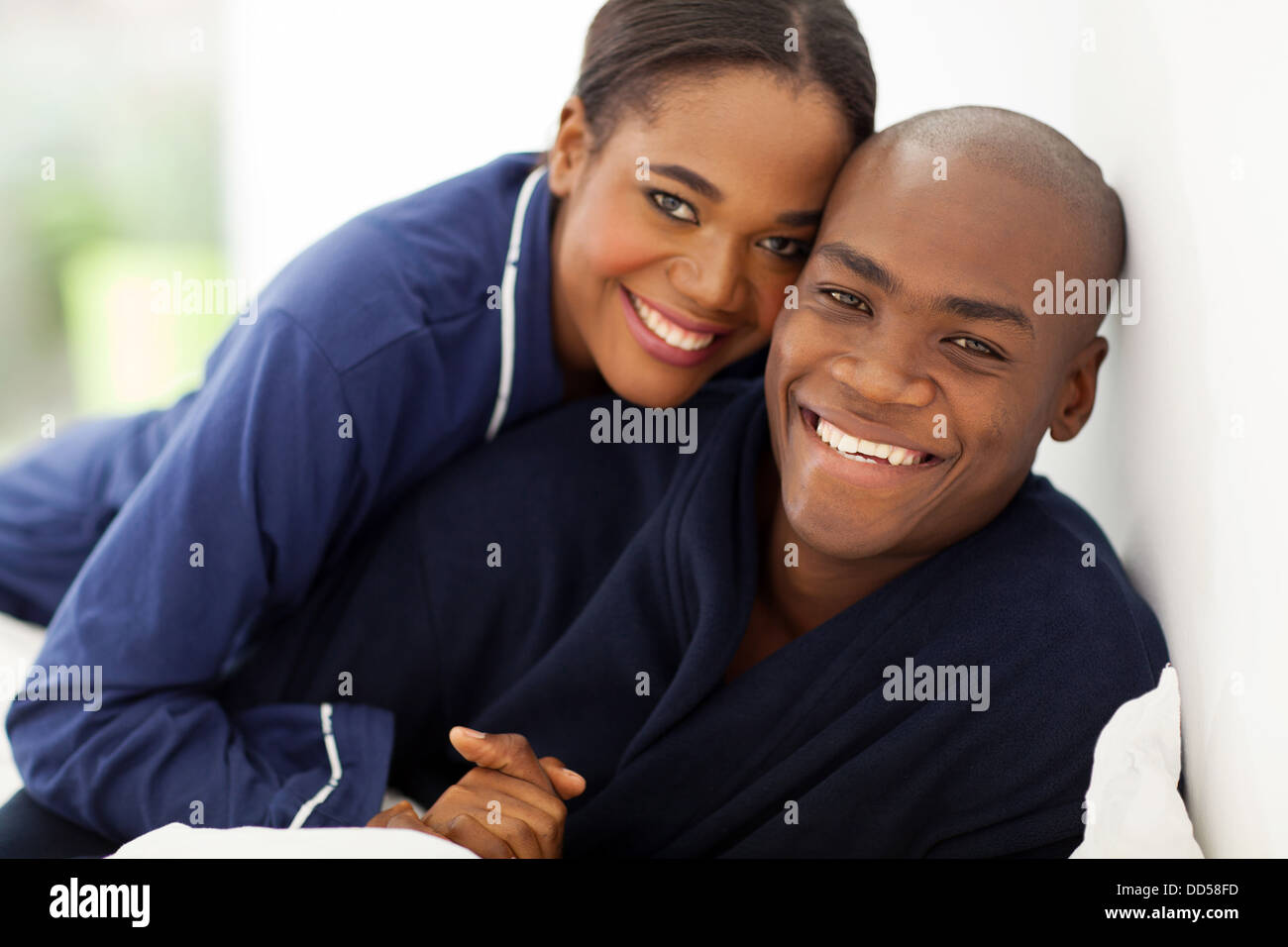 portrait of happy African couple in nightwear on bed - Stock Image