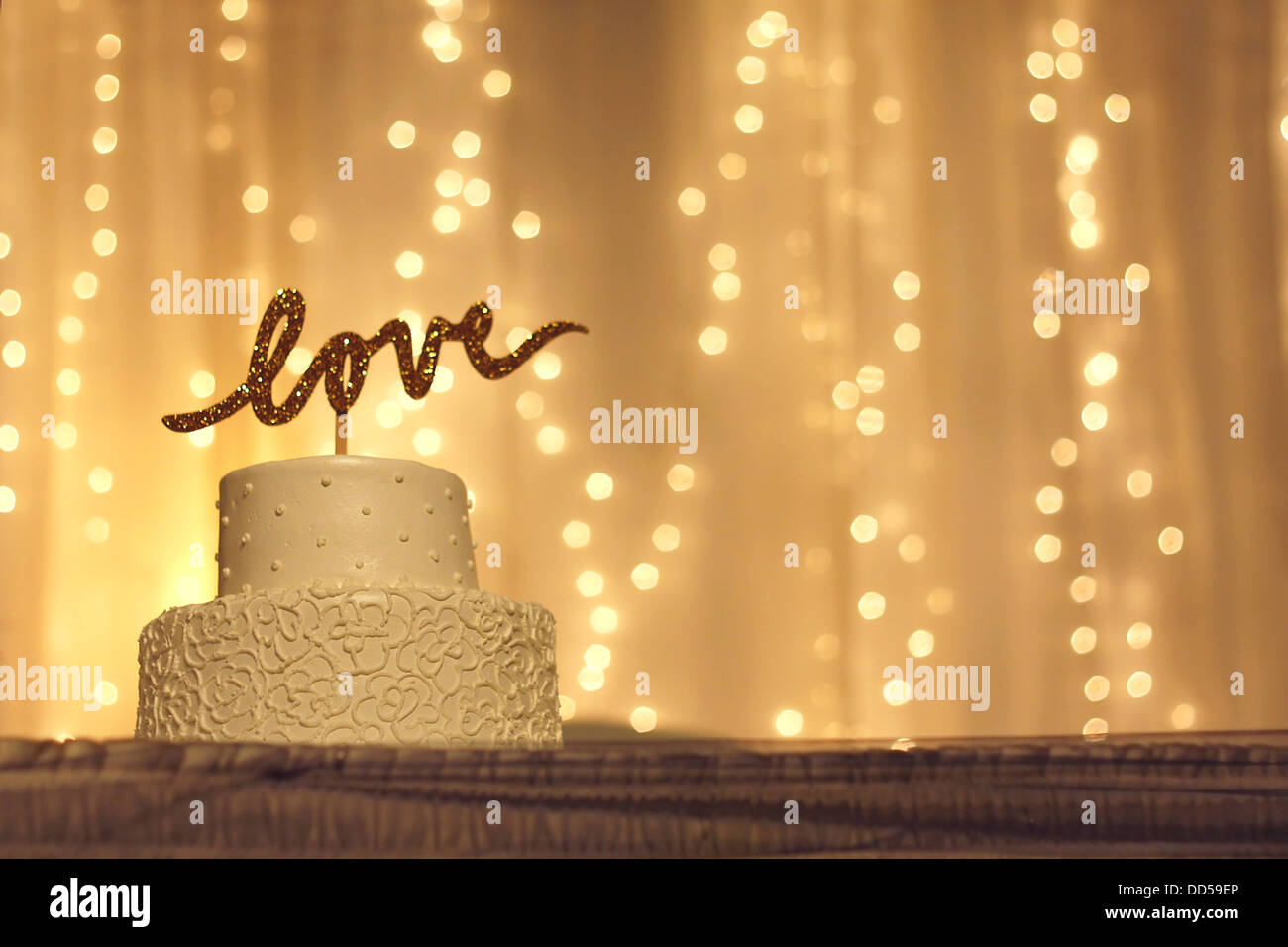 a simple white wedding cake with the word love written in sparkling ...