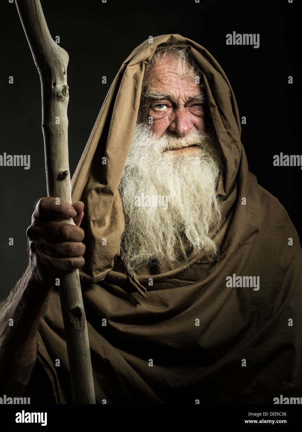old man with white beard staff and cloak looks like wizard  / Gandalf / Moses / Dumbledore - Stock Image