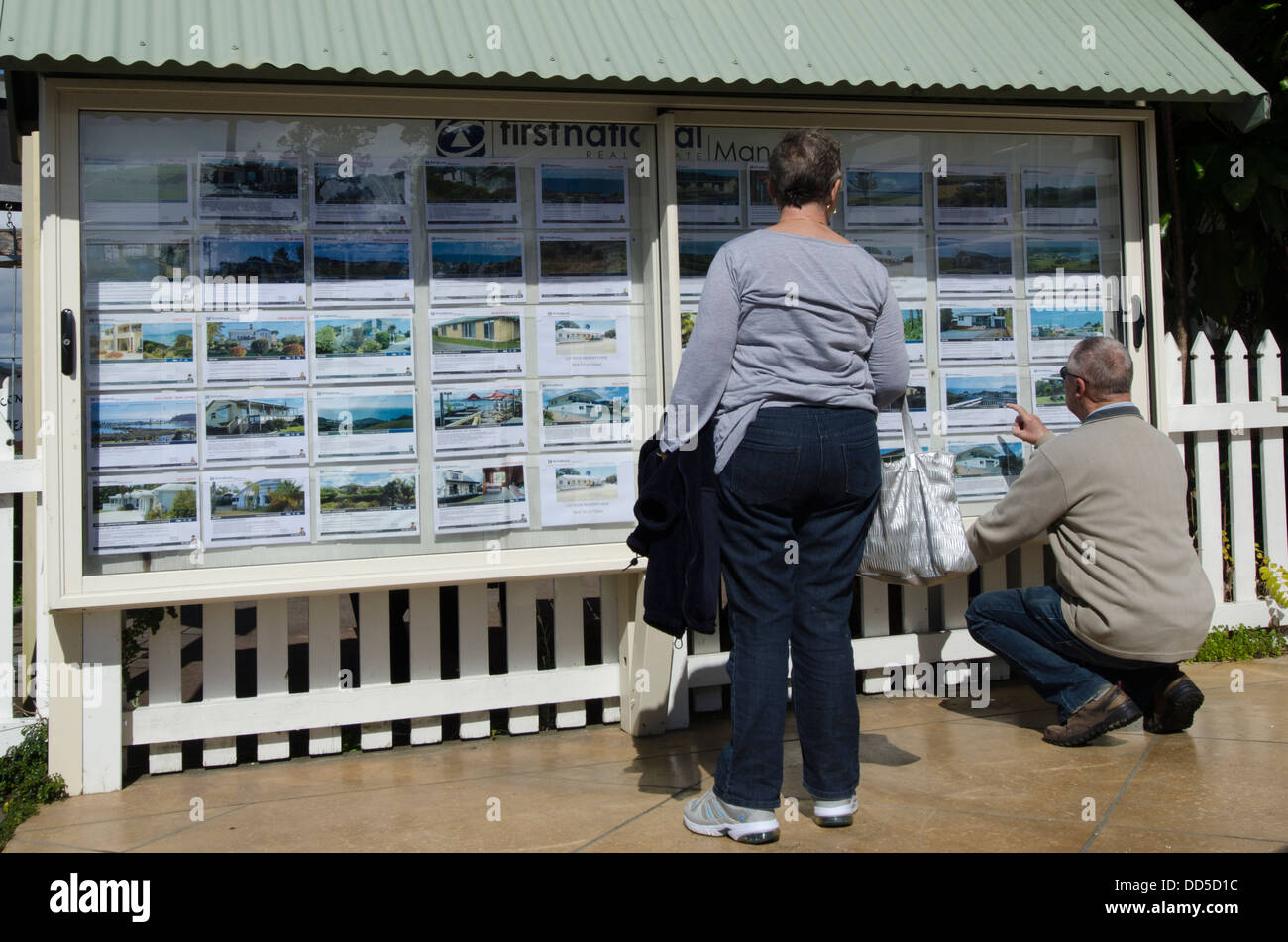 Couple looks at house listing on a signpost of Real Estate office in New Zealand - Stock Image
