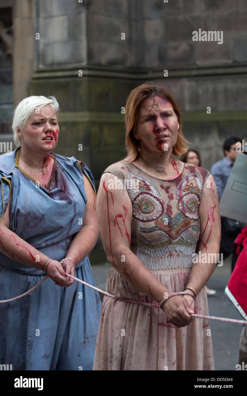 Street Theatre at the Edinburgh Festival Fringe, Greek Warriors enslave Trojan women after battle - Stock Image