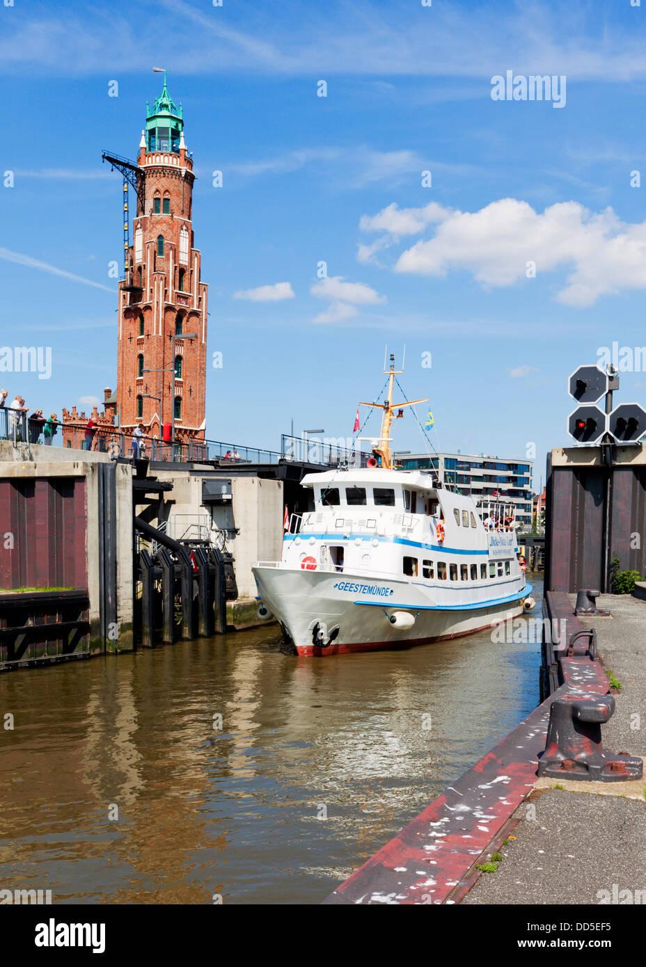 Tourist boat passing Neuer Hafen ship lock at Bremerhaven, Simon-Löschen-Turm lighthouse in background - Stock Image