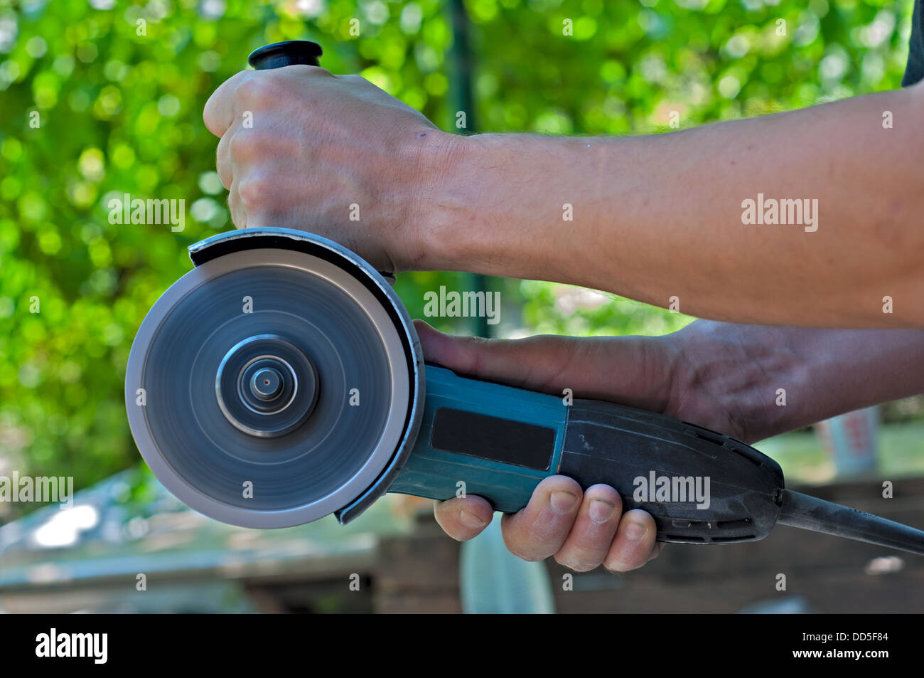 Switched on angle grinder in the man hands. Closeup. - Stock Image