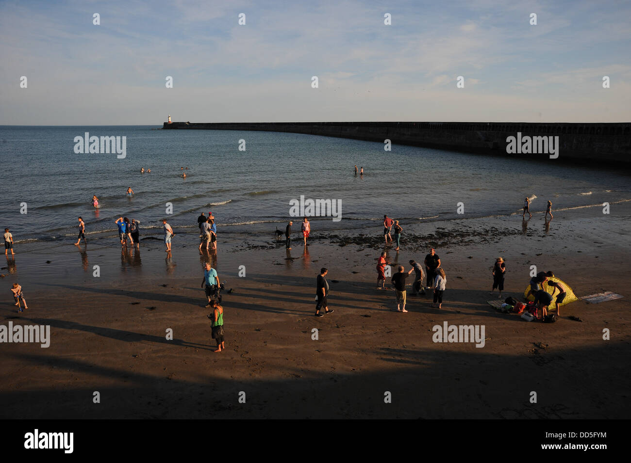 Newhaven, Sussex, UK. 26 Aug, 2013. Local residents from Newhaven enjoy the bank holiday on the closed off beach - Stock Image