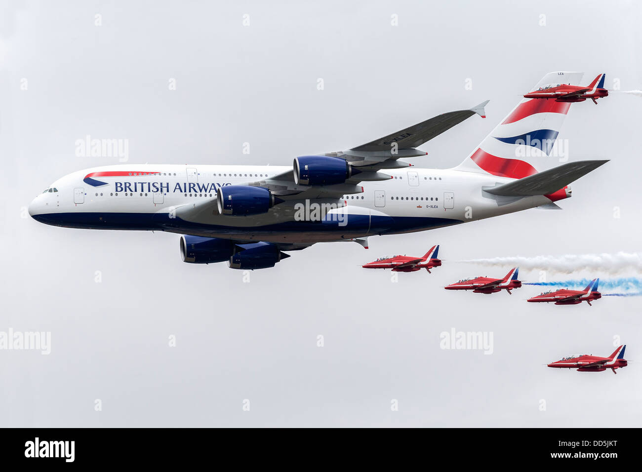 Red Arrows aerobatic team in formation with a BA A380 super jumbo - RIAT 2013 - Stock Image