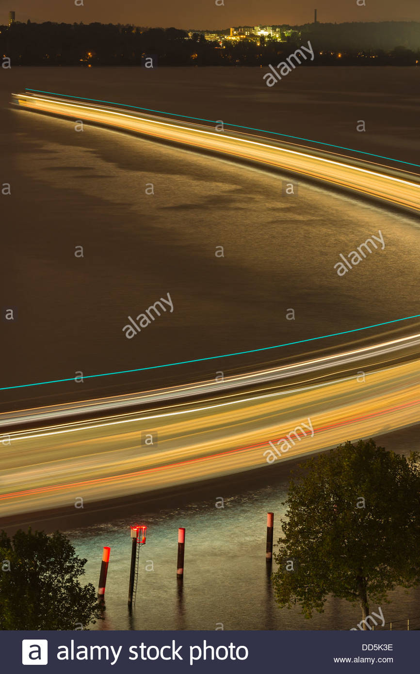 Germany, Ferry sailing out of Meersburg harbour by night - Stock Image