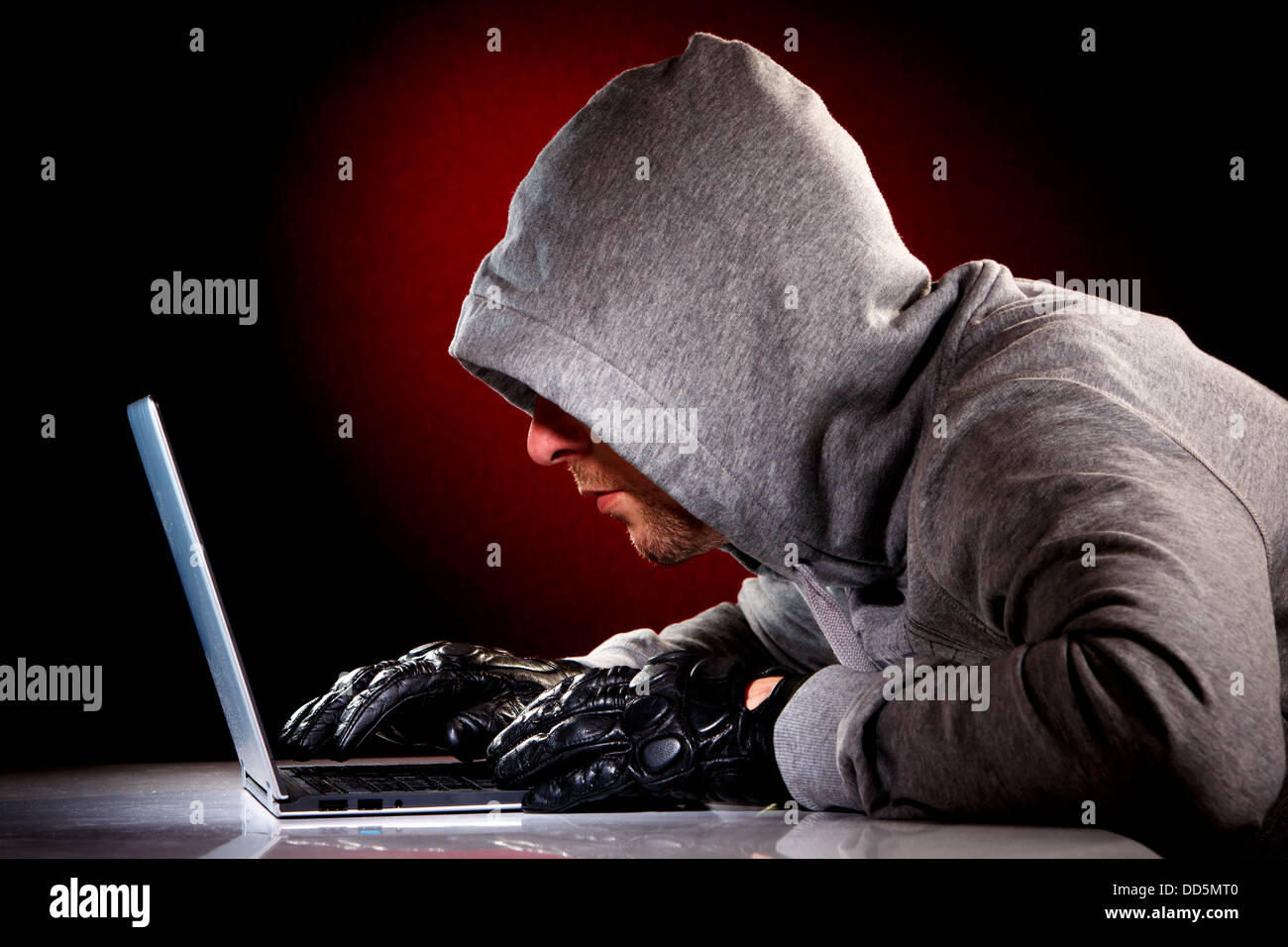 Hacker in a sunglasses with laptop. - Stock Image