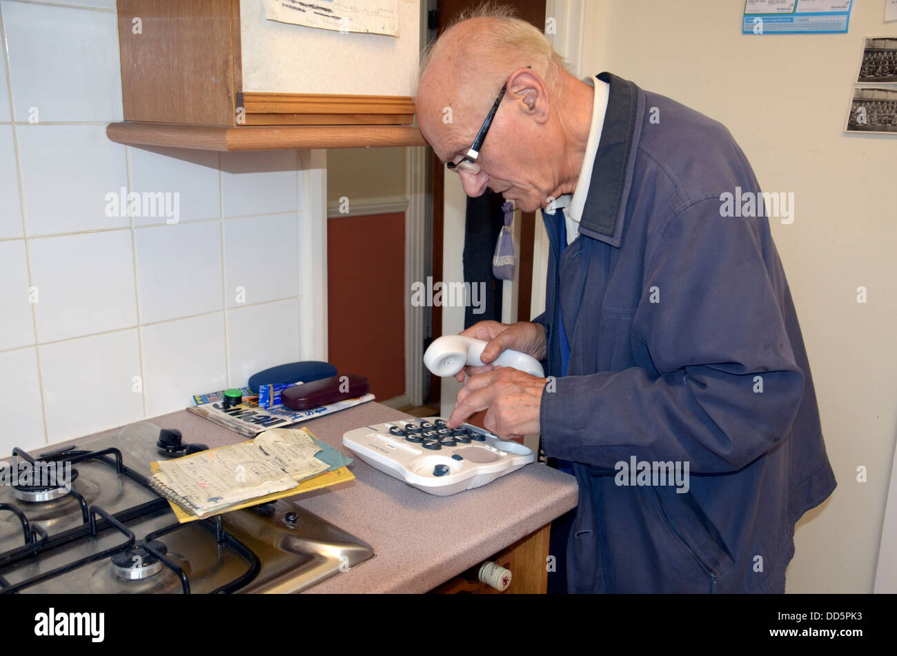 An elderly man making a phone call using his landline in his kitchen. - Stock Image