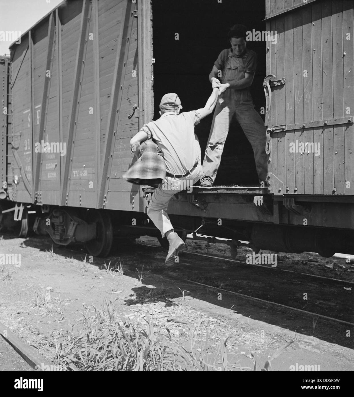 Helping a man hop a freight at Bakersfield, California, 1930s. (BSLOC_2013_8_196) - Stock Image