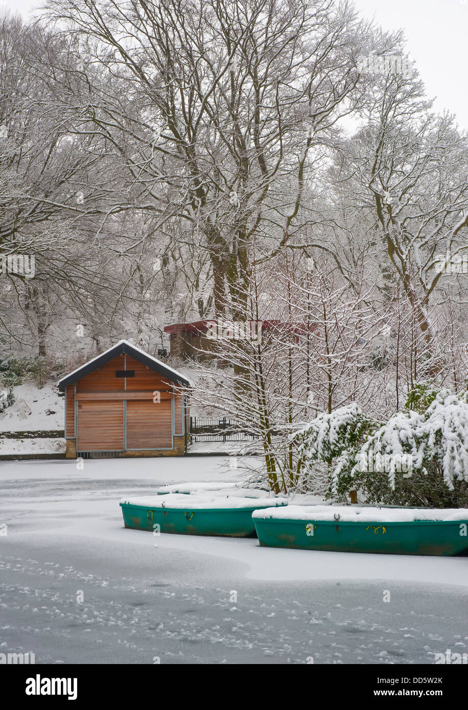 snow covered rowing boats on the boating lake at SHibden Park in Halifax,Calderdale,West yorkshire - Stock Image