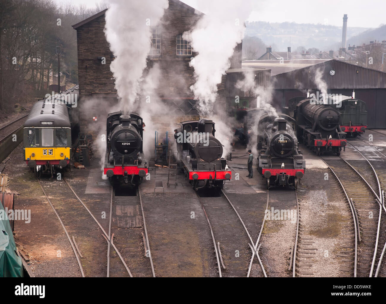 a row of steam locomotives and a classic 1960s diesel engine warming up prior to a gala day in Haworth - Stock Image