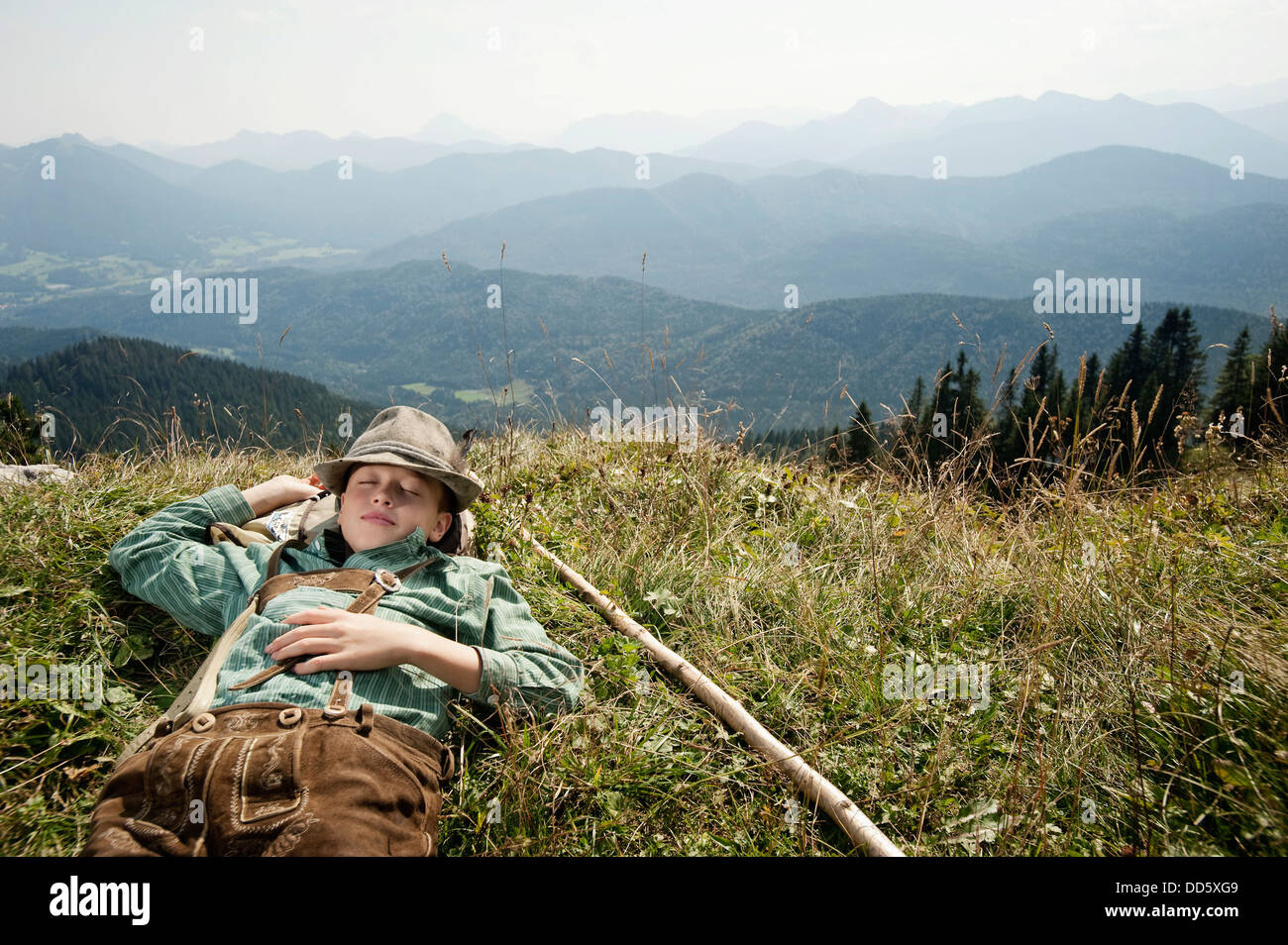 Germany, Bavaria, Boy in traditional clothing sleeps in the mountains - Stock Image