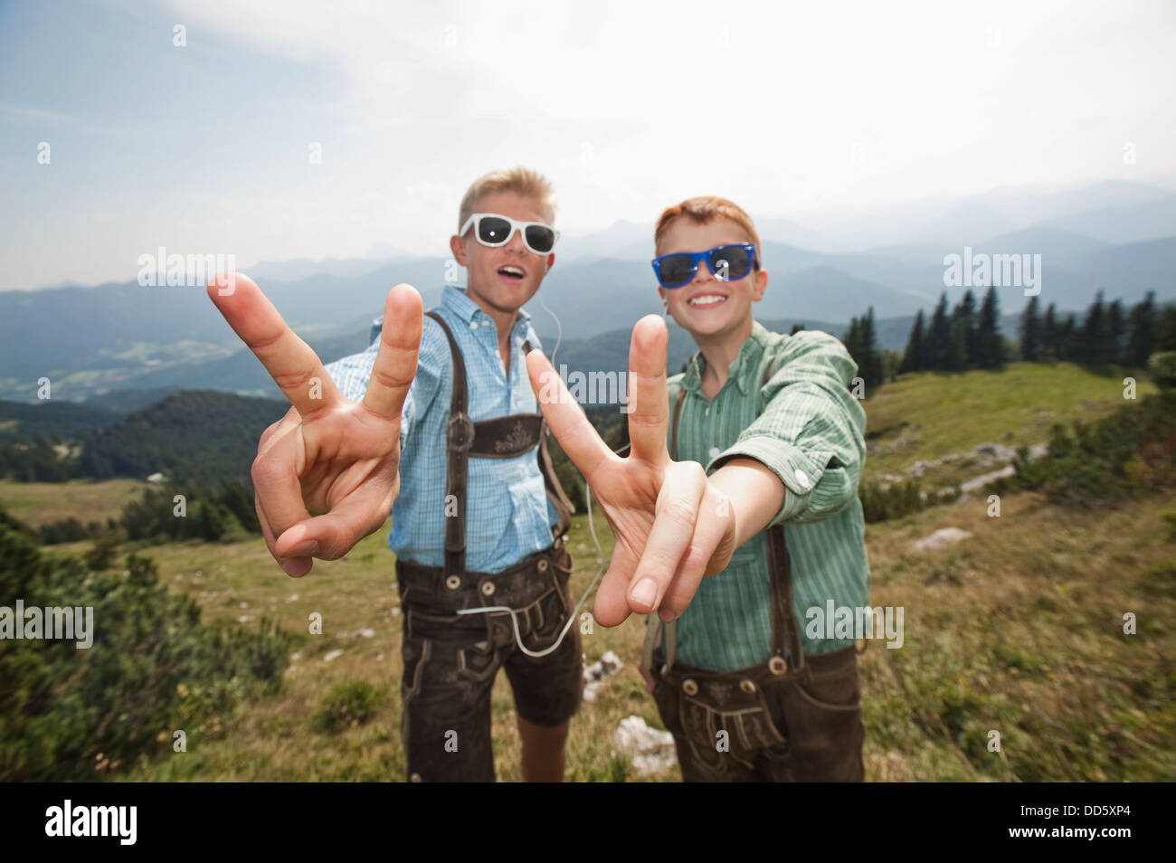 Germany, Bavaria, Two boys with sunglasses making gestures in mountains - Stock Image