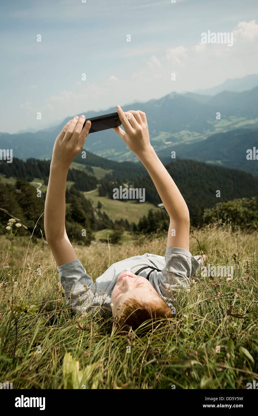 Germany, Bavaria, Boy lying on back in mountains uses a smart phone - Stock Image