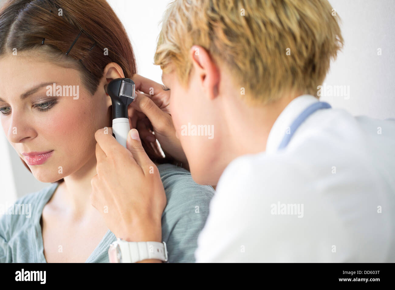 ENT physician Examining the Ear from Female Patient Stock Photo