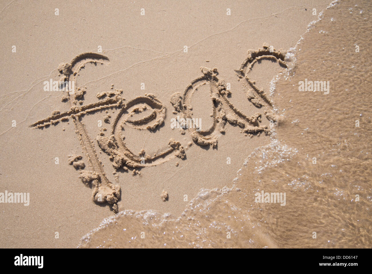 The word 'fear' written in the sand. - Stock Image