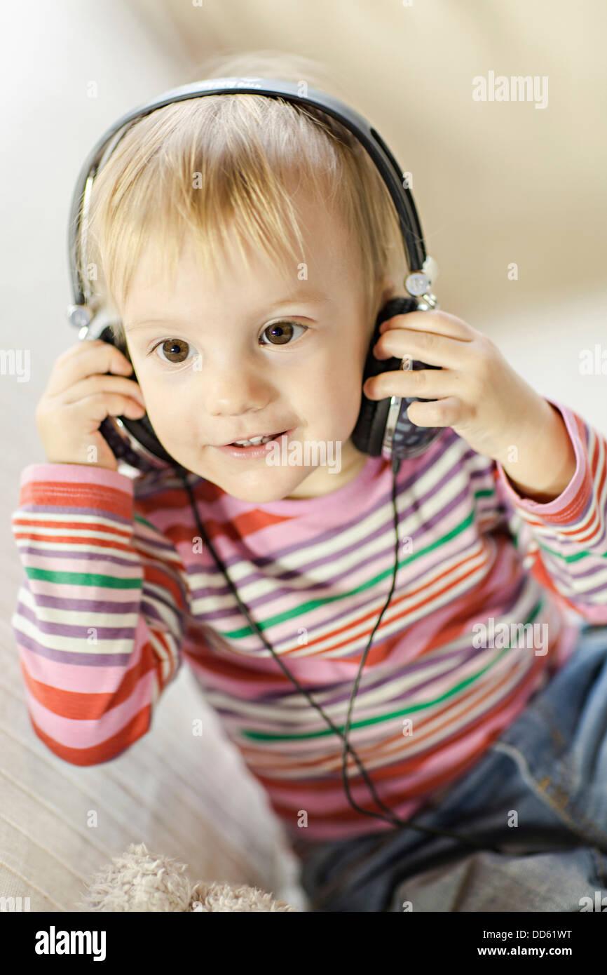 Toddler boy listens to music wearing headphones, Osijek, Croatia, Europe - Stock Image
