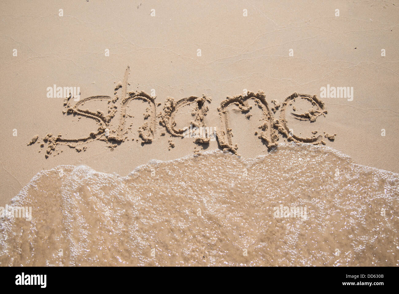 The word 'shame' written in the sand, being washed away by a wave. - Stock Image