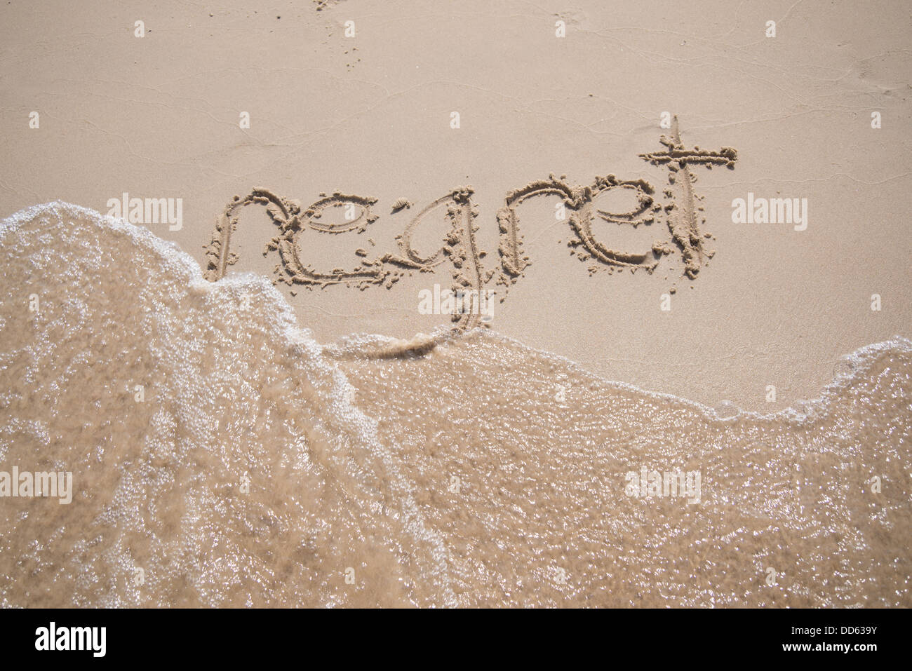 The word 'regret' written in the sand, being washed away by a wave. - Stock Image