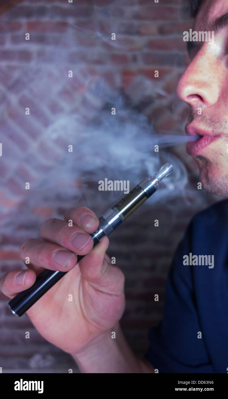 Male breathing out the vapor from an electronic cigarette - Stock Image