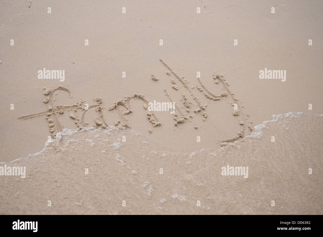 The word 'family' written in the sand, being washed away by a wave. - Stock Image