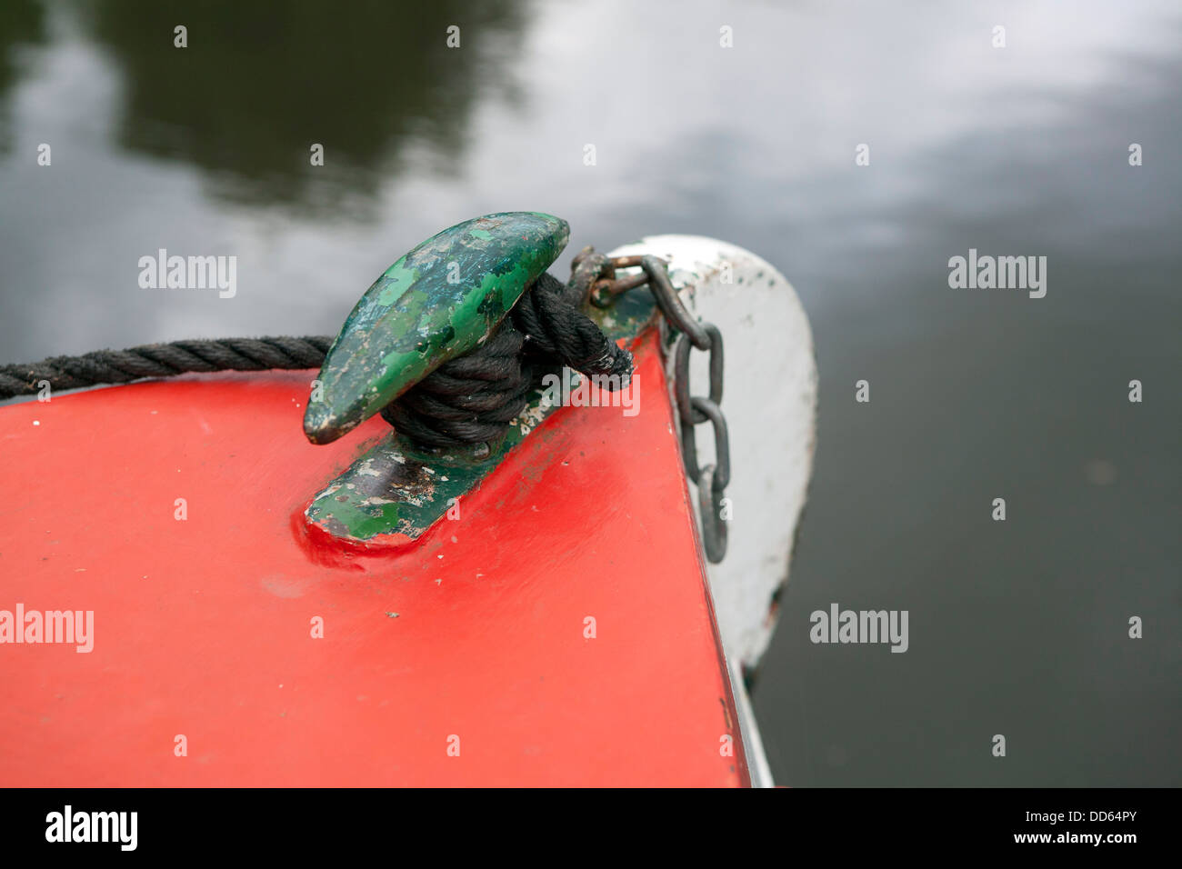 The bow of a Narrow boat's (barge) Iron fixing point, the boat is painted in bright red and green. The paint - Stock Image
