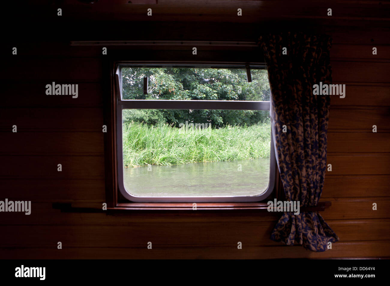 The view looking out of a window on a narrow boat that's floating on the River Kennet and Avon, Berkshire, England. - Stock Image