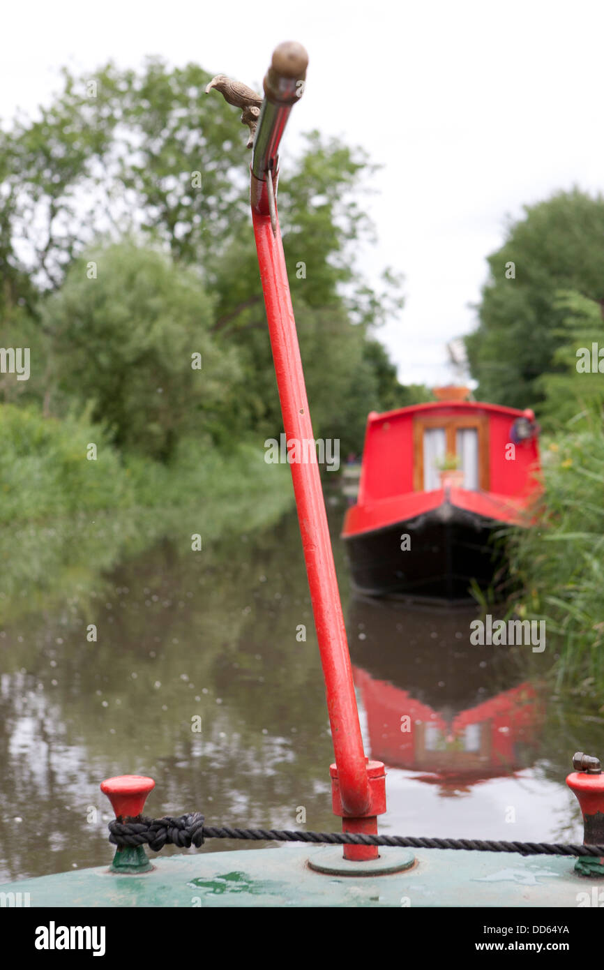 The Tiller of a narrow boat, a red barge is moored up in the background. - Stock Image
