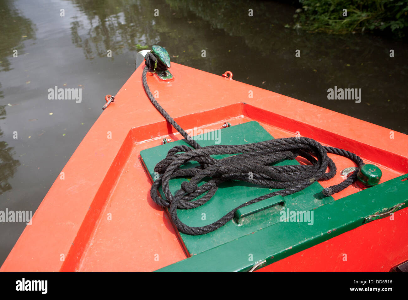The bow of a red and green narrow boat cruising on a canal - Stock Image