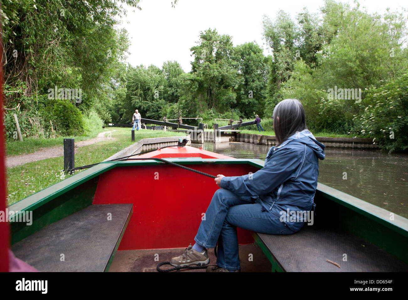 A woman holding a rope securing a narrow boat (Barge) whilst a Lock is opened in the distance. - Stock Image