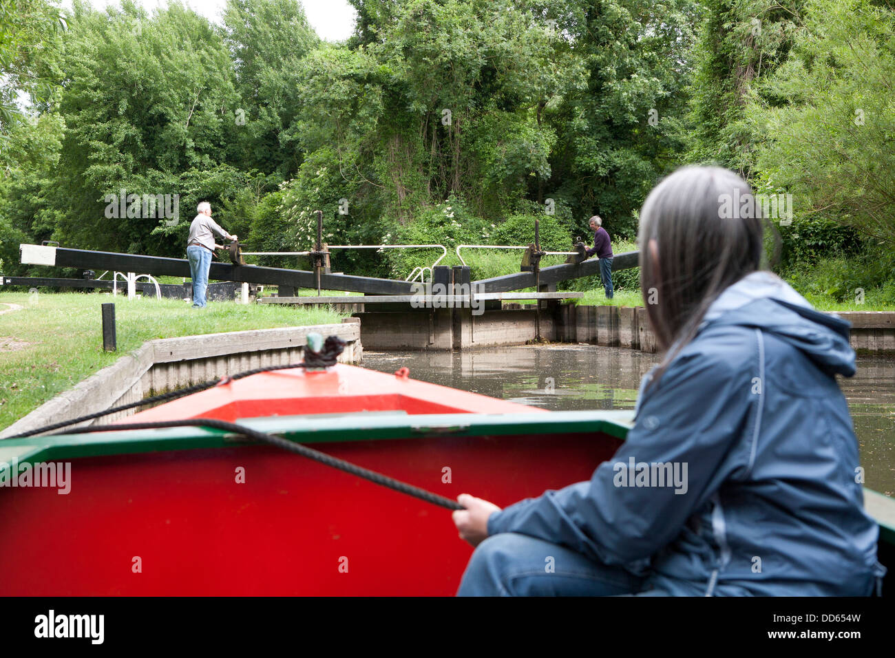 A close view ofwoman holding a rope securing a narrow boat (Barge) whilst a Lock is opened in the distance. - Stock Image