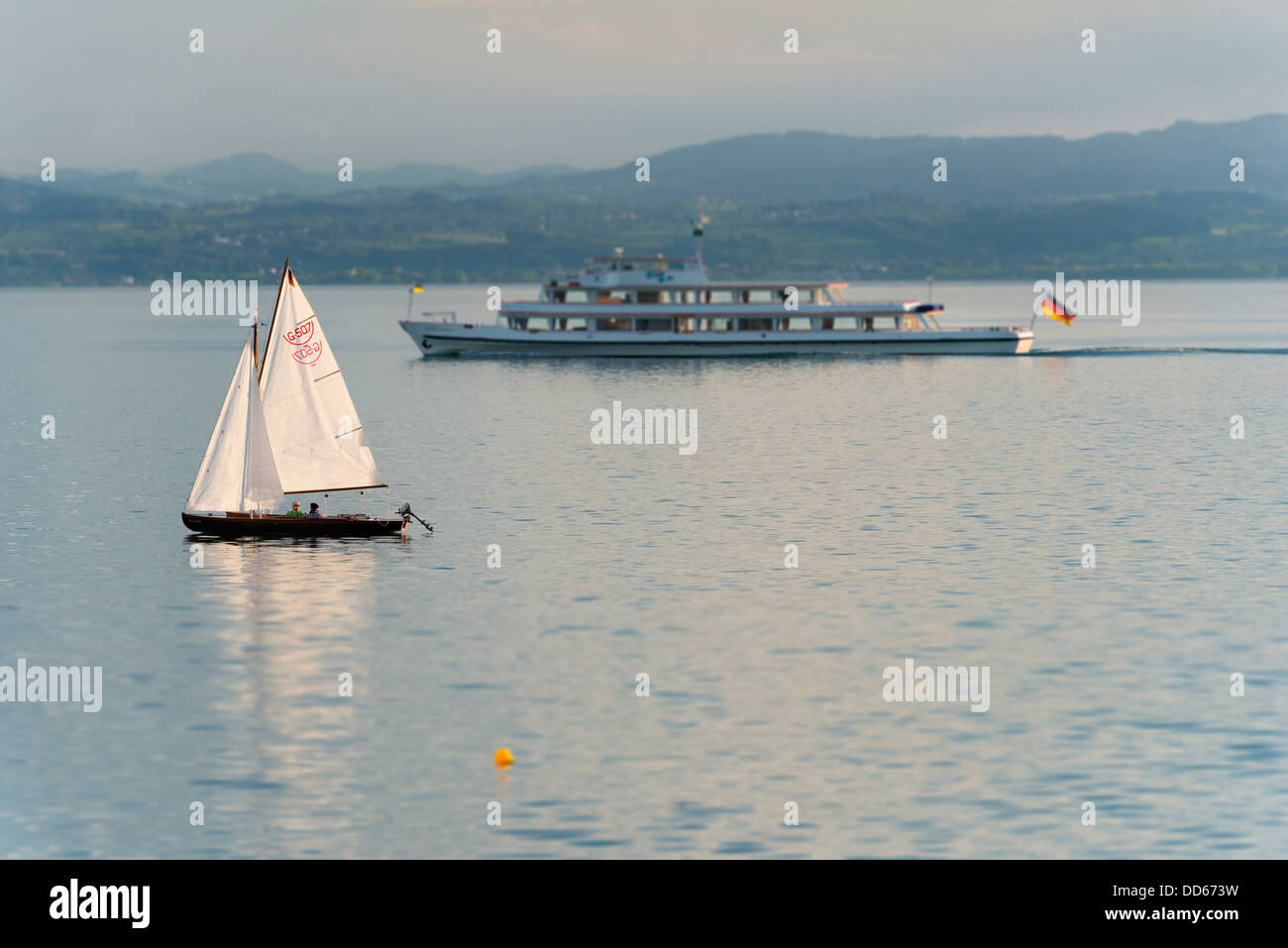 Germany, View of passenger ship passing sailing boat in lake constance - Stock Image
