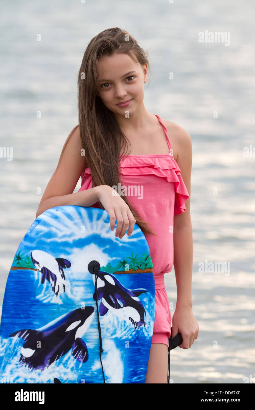 Pretty Teen Girl With Her Surfing Board On The Beach Stock