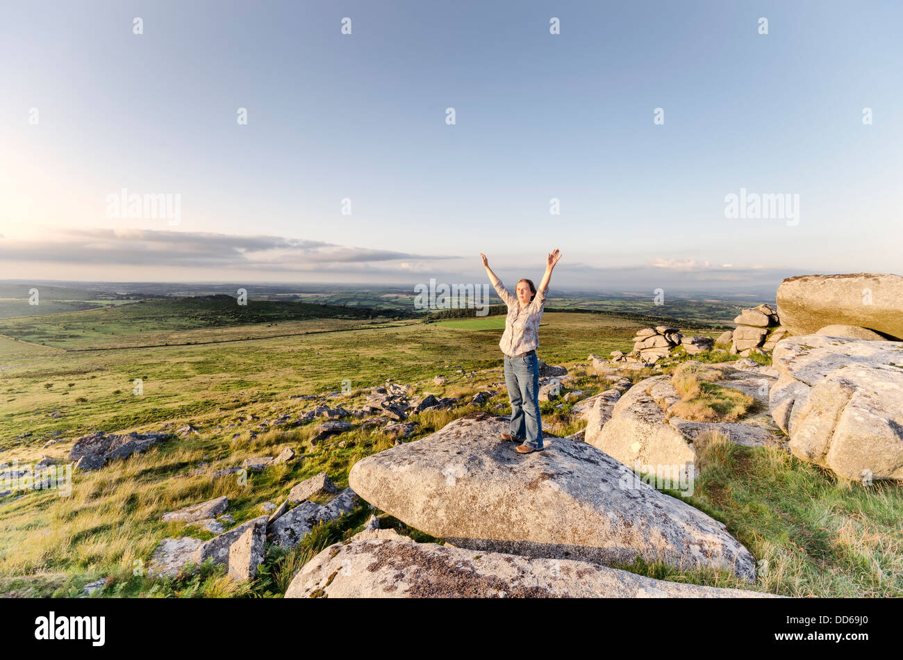 Woman standing with arms outstretched on on top of Kilmar Tor on Bodmin Moor in Cornwall, vintage effect. - Stock Image