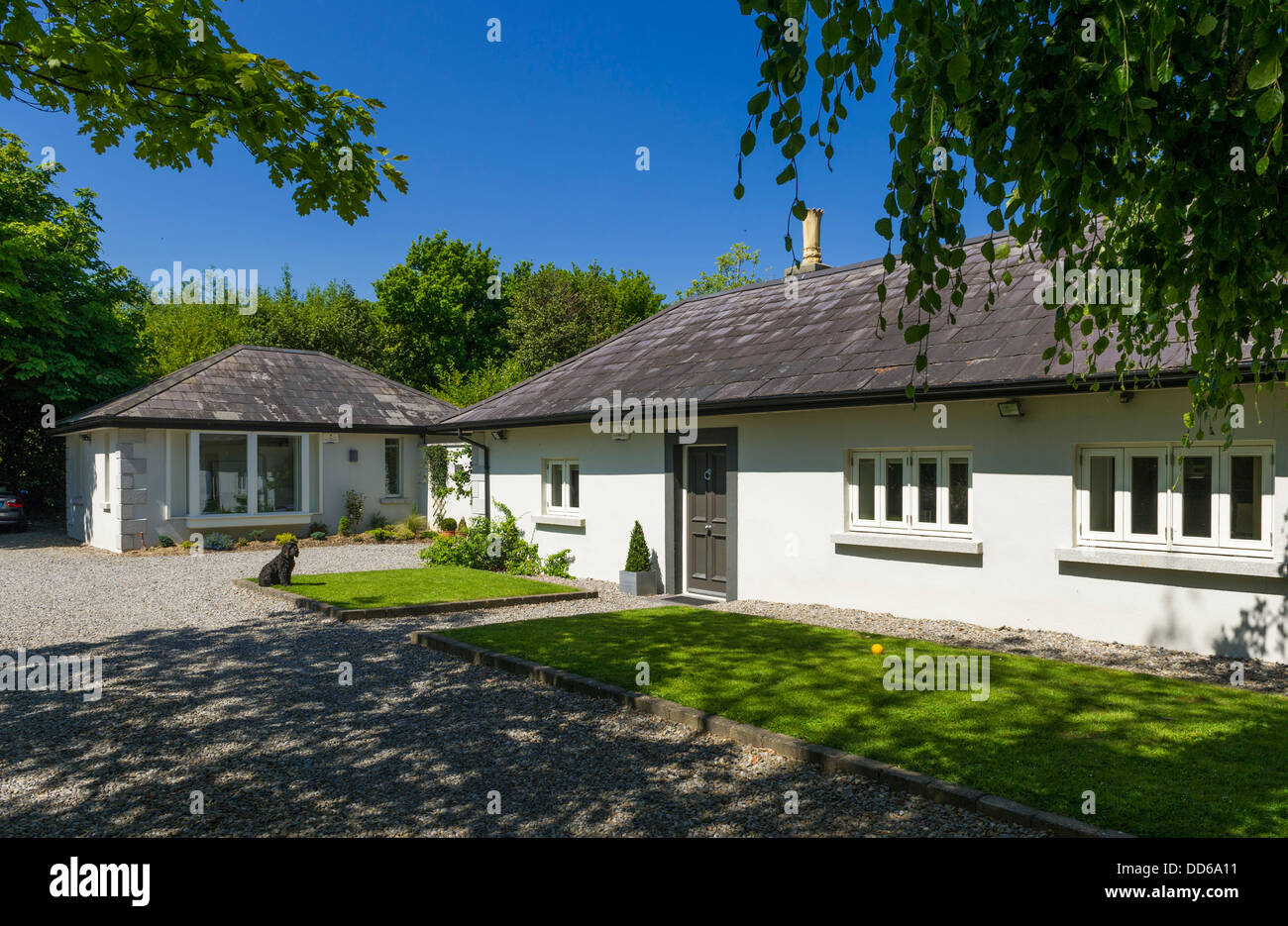 House bungalow exterior with separate home office in the garden - Stock Image