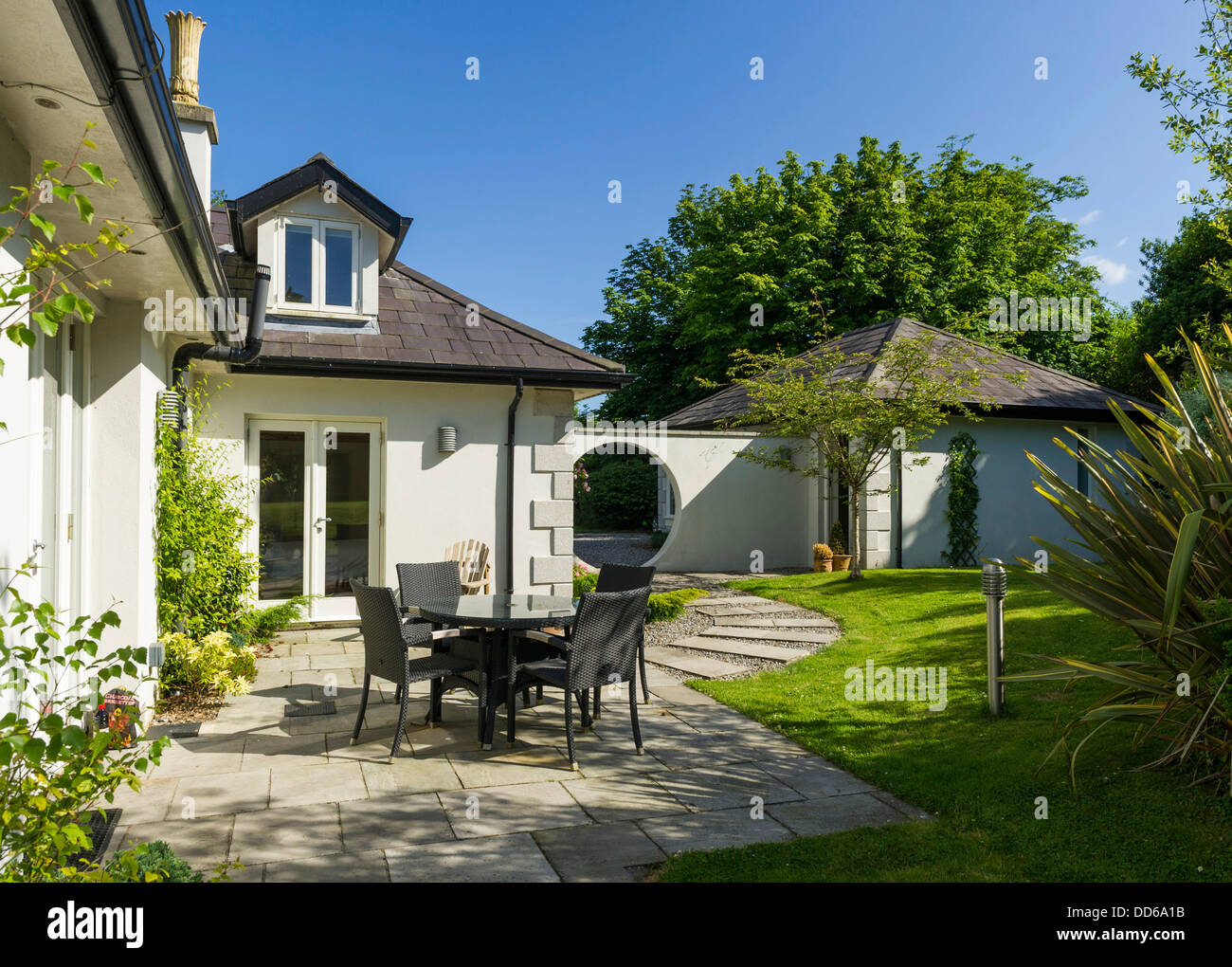 Patio with table and chairs at a residential home in the summer - Stock Image