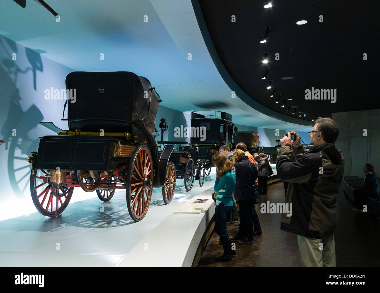 Visitors looking at an exhibit of old cars in the Mercedes Museum ...