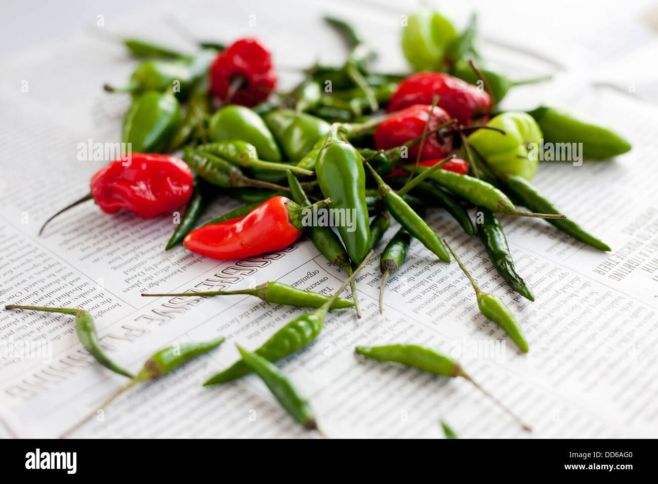 Pile of mixed chilli peppers, on a newspaper background. Side view. Bird's eye, Scotch Bonets, Jalapeños. Stock Photo