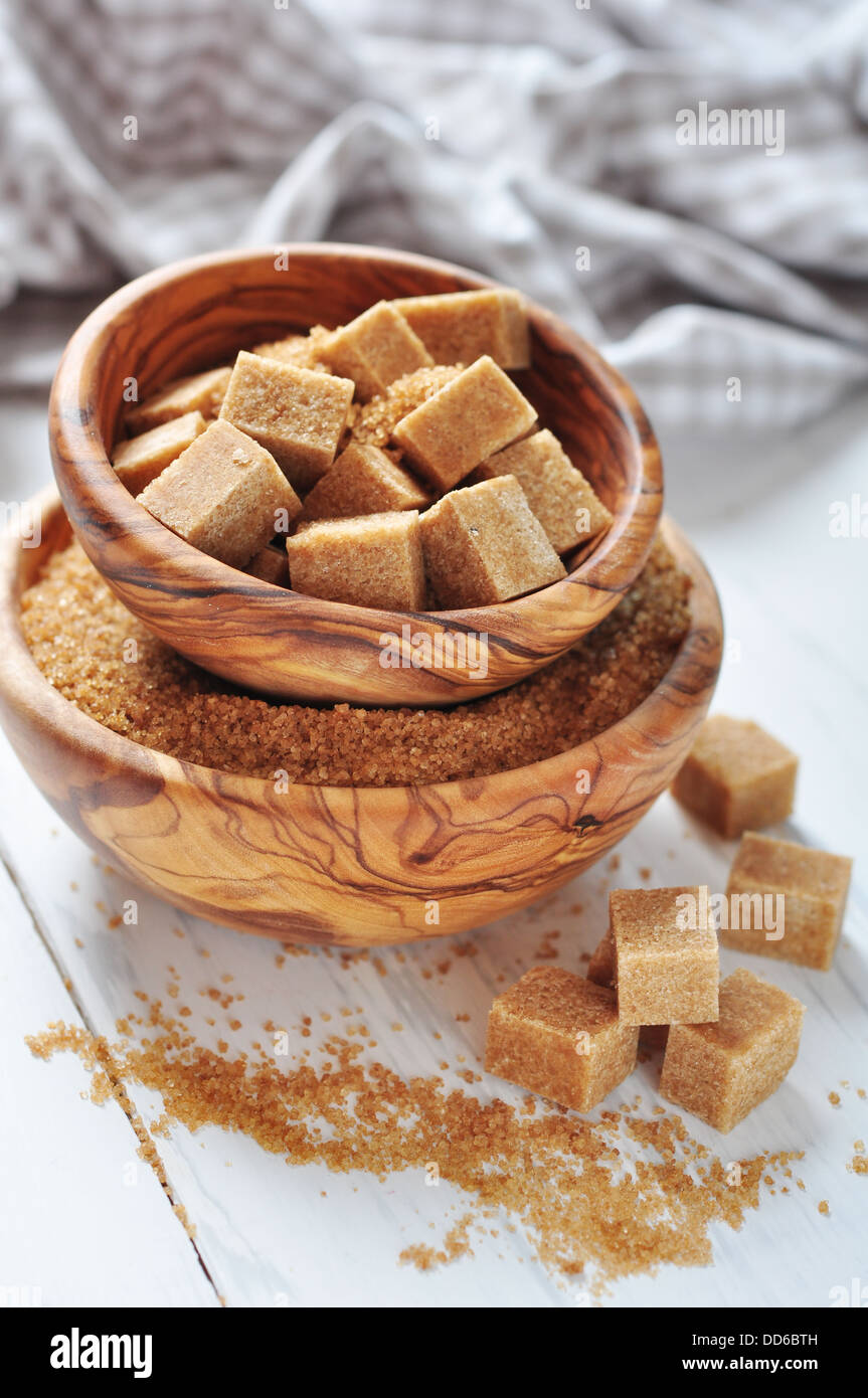 Brown sugar in wooden bowl on white wooden background - Stock Image