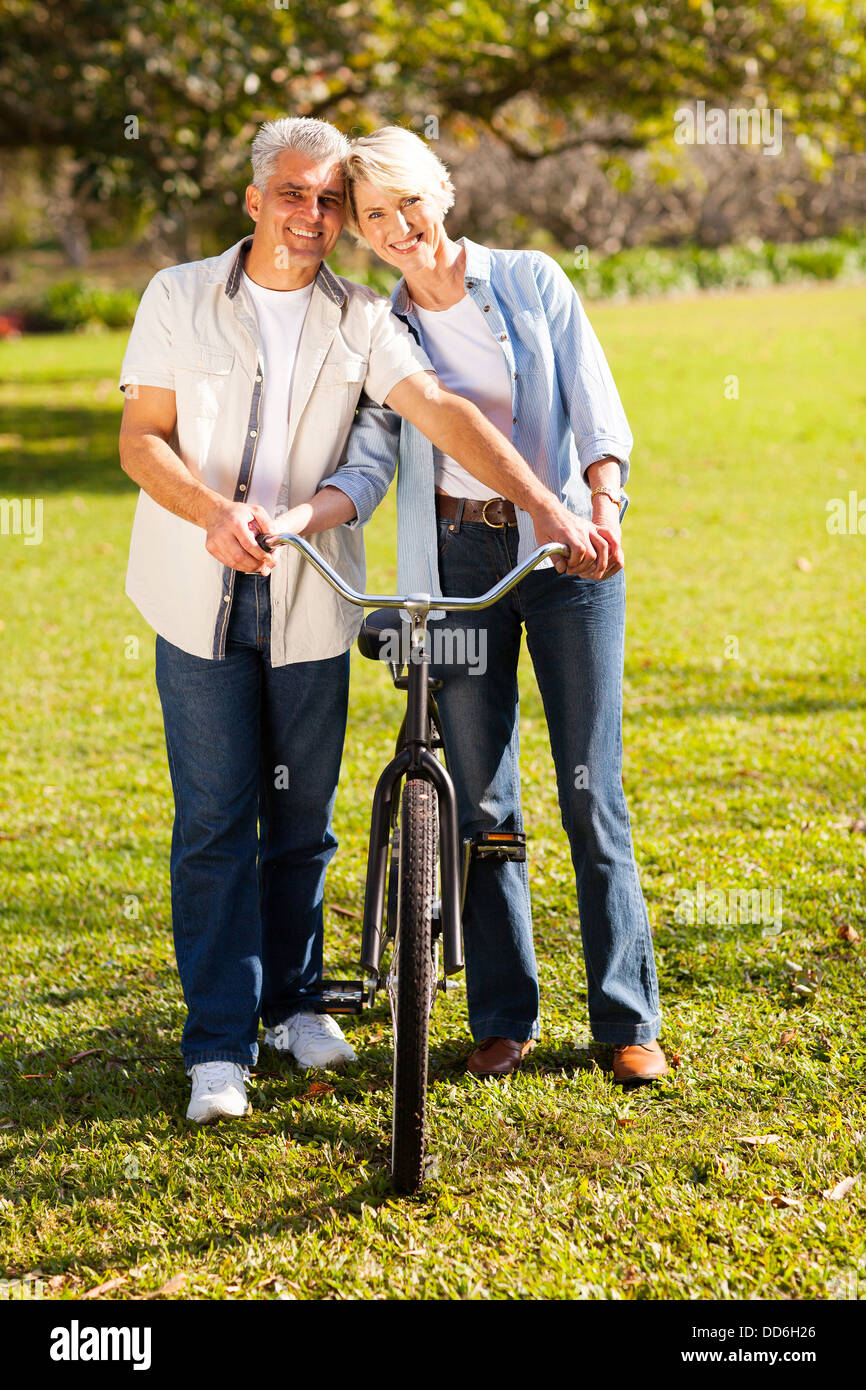 cheerful middle aged couple walking a bike at countryside - Stock Image