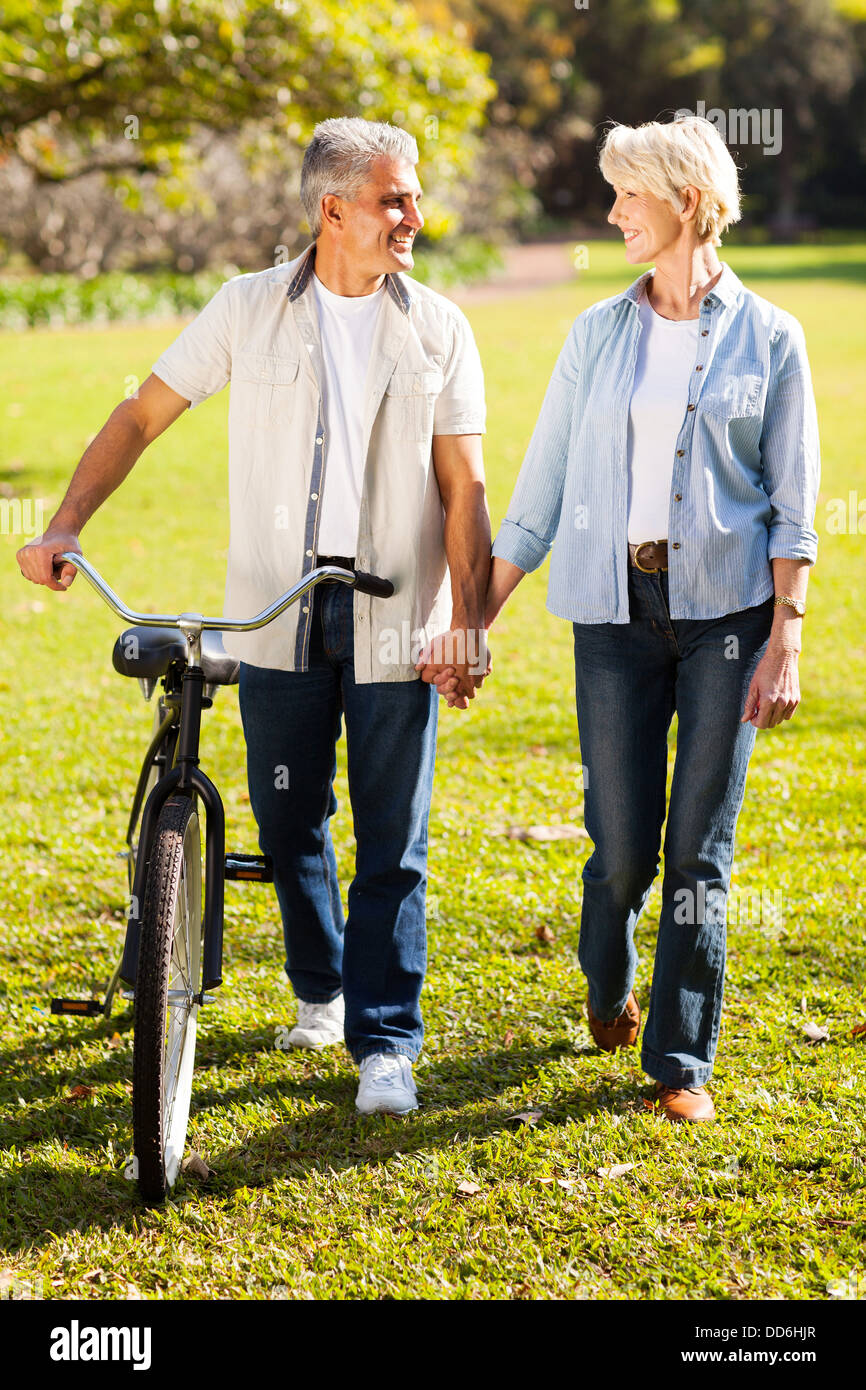 beautiful senior couple walking a bike in park holding hands - Stock Image