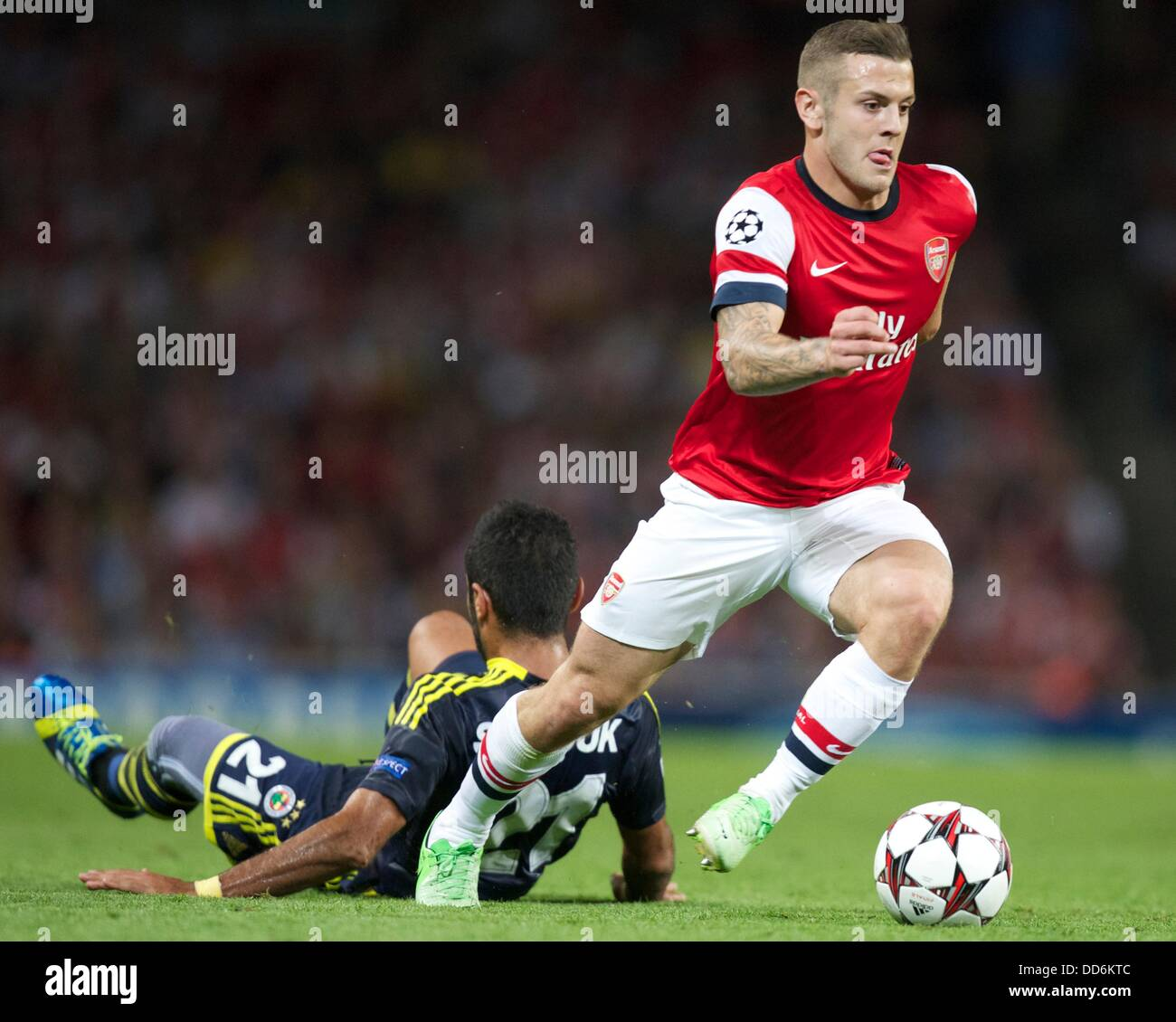 London, UK. 27th Aug, 2013. Jack Wilshere of Arsenal leaves Selcuk Sahin of Fenerbahce on the floor during the Champions - Stock Image