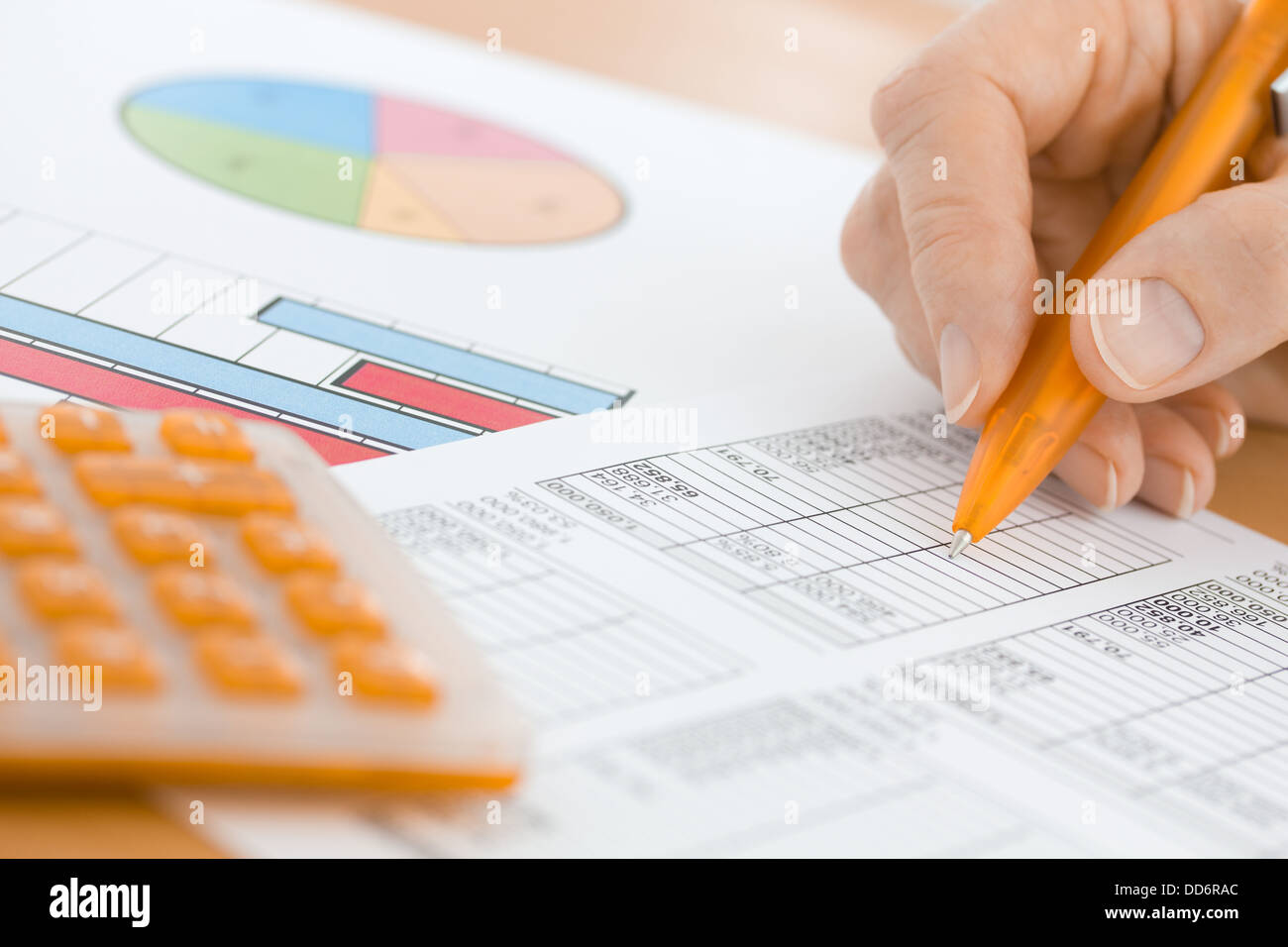Hand with Orange Pen and Calculator Checking Spreadsheet Figures - Stock Image