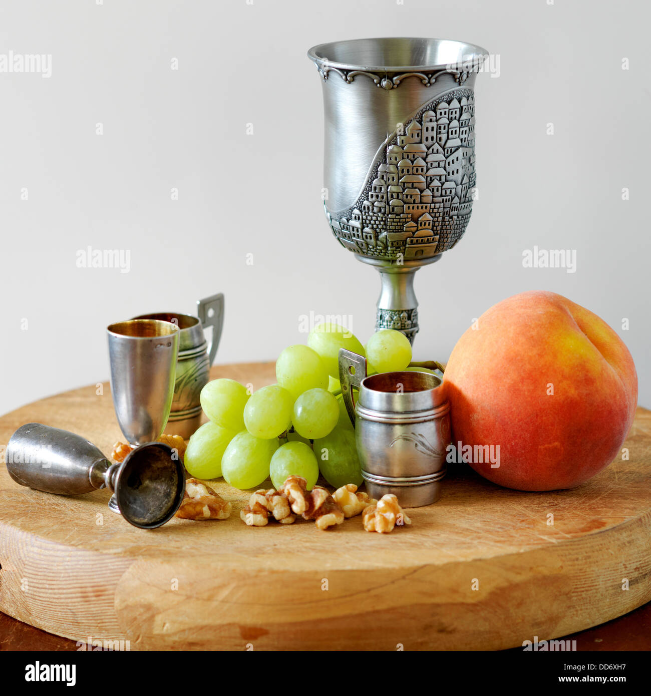 Wine chalice with walnuts grapes and a peach on the top of a cutting board - Stock Image