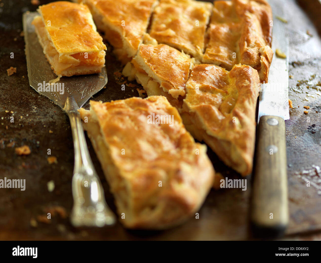 Freshly backed apple pie on the backing sheet with the server and a knife - Stock Image