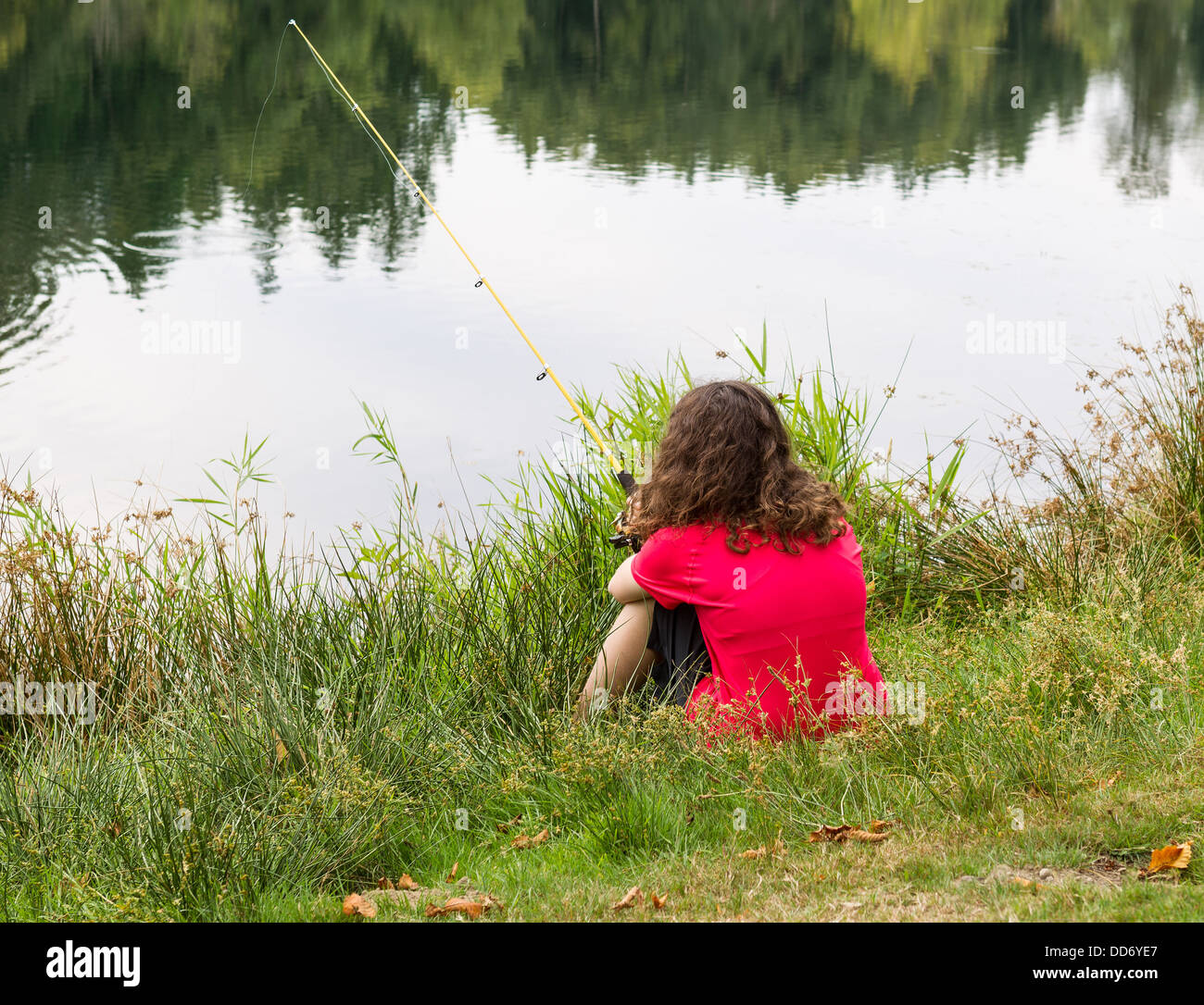 Photo of young girl patiently waiting for fish to bite with lake and trees in background - Stock Image